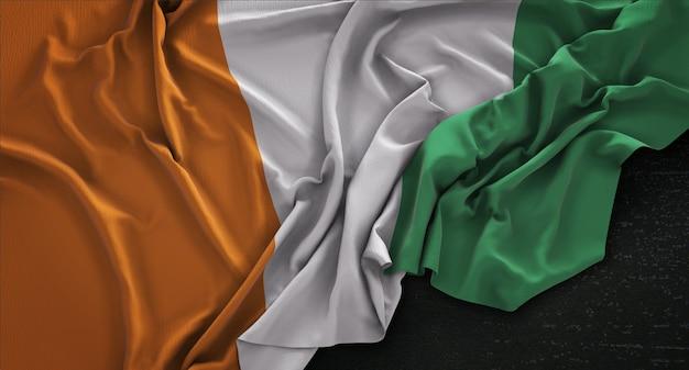 Ivory coast flag gerimpelde op donkere achtergrond 3d render