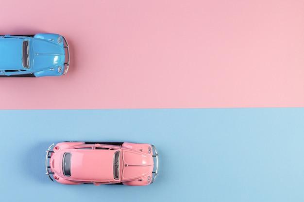 Izhevsk, rusland, 15 februari 2020. kleine vintage retro speelgoedauto's op een roze en blauwe achtergrond