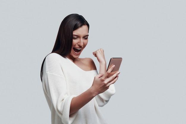 Ja! aantrekkelijke jonge vrouw die smartphone gebruikt en gebaren maakt terwijl ze tegen een grijze achtergrond staat
