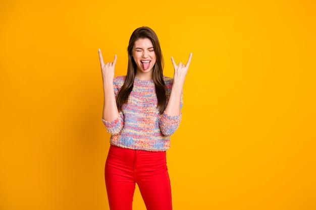 Ja cool! gek opgewonden vrolijk tienermeisje geniet van weekendconcert sluit ogen verheugen horens symbool tonen tong uit dragen rode broek broek trui geïsoleerde glans kleur