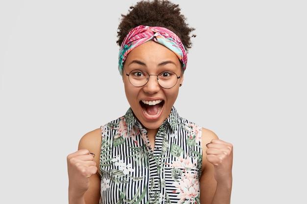 Ja, dat is geweldig! schot van blije afro-amerikaanse vrouw met knapperig haar, schreeuwt van geluk, balde vuisten, maakt winnend gebaar, bereikt alles in het leven, draagt elegante blouse