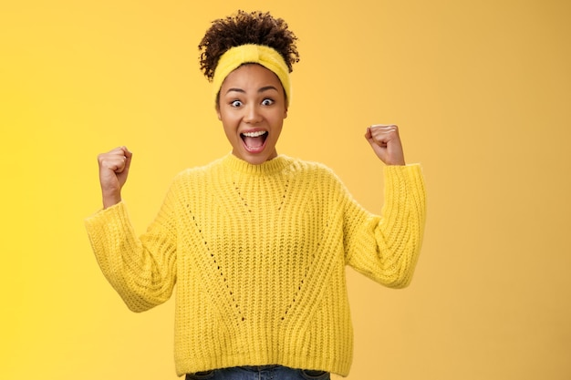 Ja, eindelijk prijs de mijne. opgewonden verrast geamuseerd afro-amerikaans meisje viert overwinning prestatie gejuich glimlachend breed schreeuwen rust vuisten triomfantelijk succes, staande gele achtergrond.