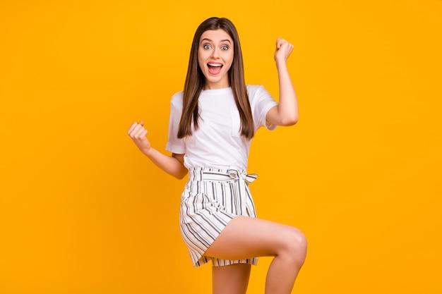 Ja! foto van aantrekkelijke gekke blije dame heft vuisten luid schreeuwen kampioen dragen casual wit t-shirt gestreepte zomer mini korte broek geïsoleerde gele kleur muur