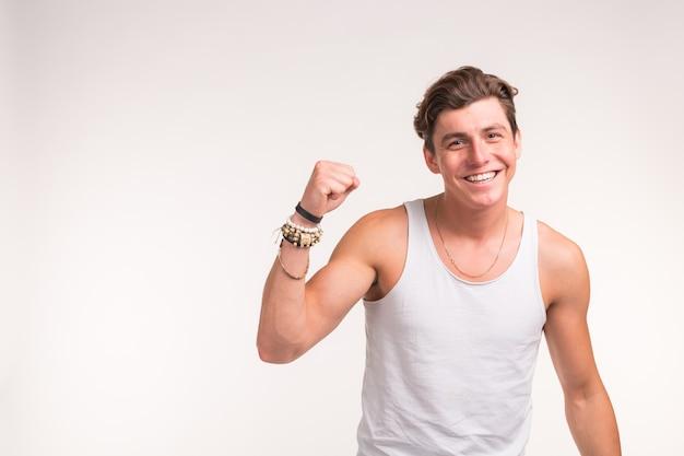 Ja gebaar, fitness en mensen concept - portret van succesvolle knappe man met opgeheven handen op witte achtergrond met kopie ruimte
