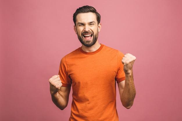 Ja! gelukkige winnaar! gelukkige jonge knappe mens die en mond gesturing houden open terwijl status tegen roze muur.