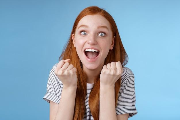 Ja geweldig nieuws geweldig. aantrekkelijk verrast roodharige meisje juichen gelukkig gebalde vuisten schreeuwen ja bereiken doel brede ogen opgewonden vieren win loterij triomfantelijk vreugdevol, blauwe achtergrond.