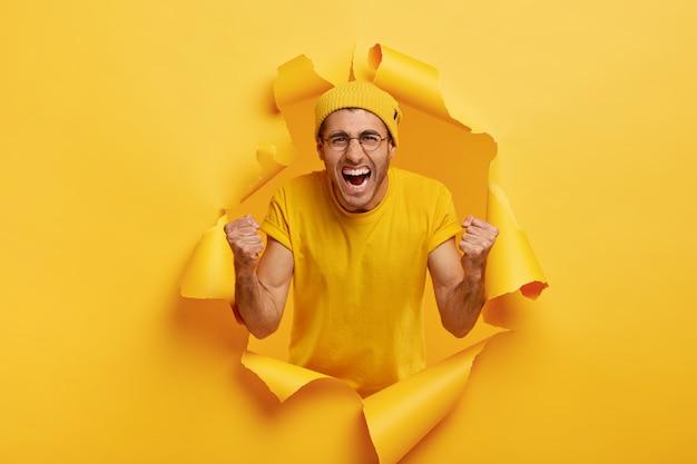 Ja, het is gelukt! triomfantelijke emotionele man roept om favoriete team, schreeuwt van vreugde, draagt een gele hoed en een t-shirt