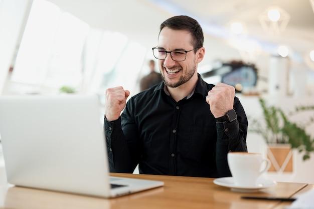 Ja, het werkt! vrolijke man met bril is blij dat het project waar hij al heel lang aan heeft gewerkt eindelijk door zijn superieuren is geaccepteerd. afstandswerk. coffeeshop op de achtergrond.
