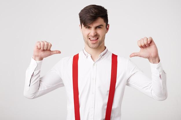 Ja, ik ben een winnaar! zelfverzekerde jonge man heeft iets belangrijks gedaan, wil blikken ontvangen die met de duim naar zichzelf wijzen, voelt zich een winnaar, leider, succesvolle man, draagt een wit overhemd