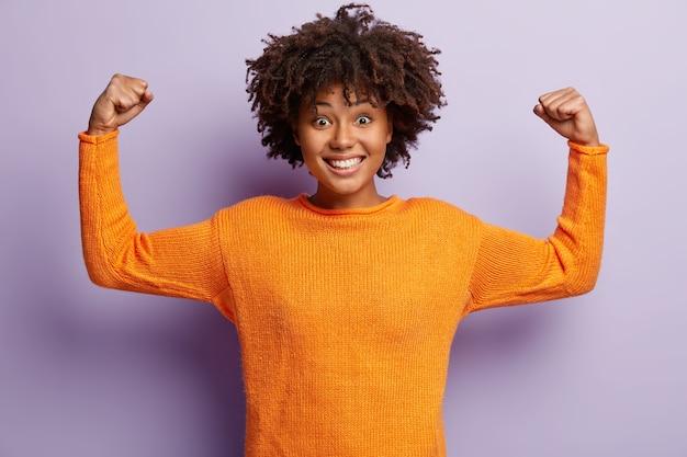 Ja, ik ben winnaar! vrolijke glimlachende donkere vrouw heft armen op, toont spieren, is krachtig