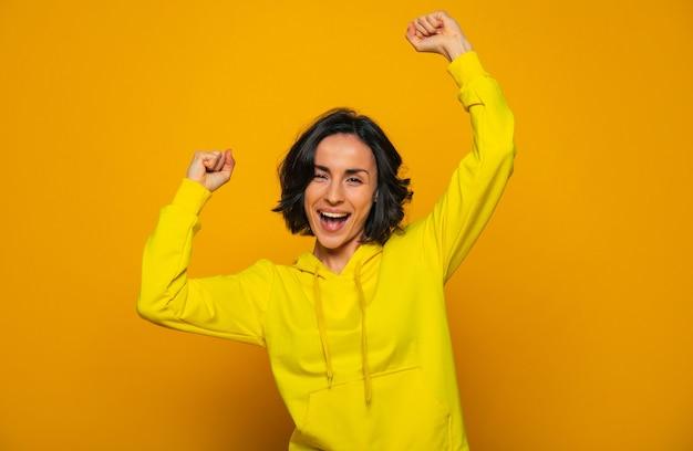 Ja! ik heb het gedaan. glimlachend tevreden meisje gekleed in een gele hoodie, de overwinning vieren met gebalde vuisten, recht kijkend.