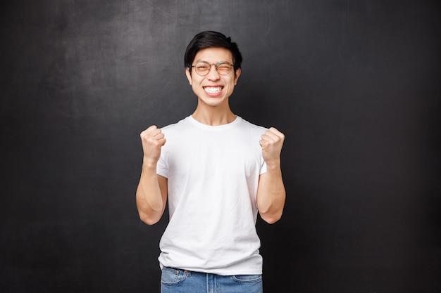 Ja ik heb het gedaan. tevreden en gelukkige aziatische kerel geslaagd voor examen, vuistpomp in succes en feest, knipoog vrolijk lachend doel bereiken, prijs of beloning winnen, zegevieren over overwinning,