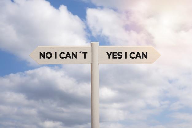 Ja, ik kan concept. houten tekenpost met tekst die op hemel wordt geïsoleerd