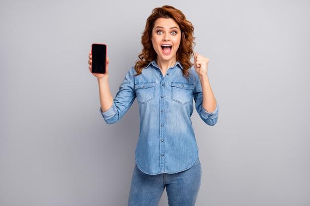 Ja, ik win een nieuw apparaat! vrolijke extatische vrouw houdt smartphone vieren het bereiken van moderne technologie overwinning vuisten heffen schreeuwen ja draag stijlvolle trendy kleding geïsoleerde grijze kleur muur