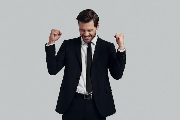 Ja! knappe jonge man in volledig pak gebaren en schreeuwen terwijl hij tegen een grijze achtergrond staat
