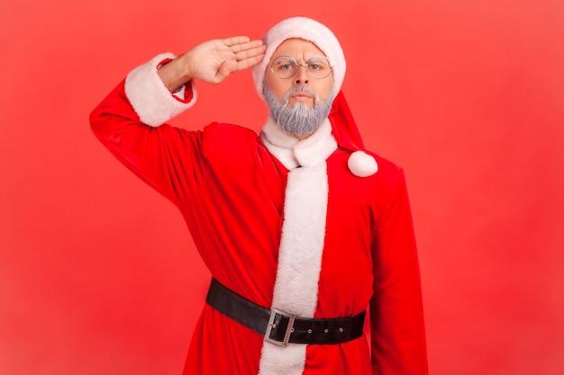 Ja meneer! de kerstman salueert met zijn arm in de buurt van de tempel en luistert aandachtig naar de bestelling.