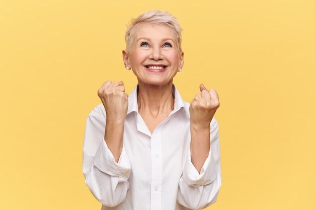 Ja! modieuze, energieke vrouw van middelbare leeftijd die zich verheugt over haar succes, het bereiken van doelen en het vervullen van dromen, dolgelukkig en extatisch is, vuisten balancerend en opkijkt, god of het universum dankt