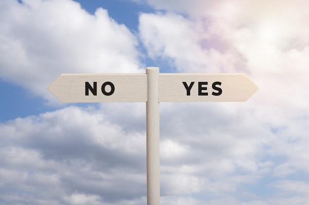 Ja of geen concept. houten tekenpost met tekst die op hemel wordt geïsoleerd
