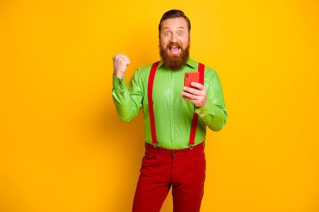 Ja, ongelooflijk! gek rood haar roodharige man gebruik mobiele telefoon winnen sociale media loterij vuisten heffen schreeuwen slijtage bretels broek broek geïsoleerde heldere gele kleur