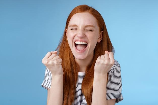 Ja prestatie doel levensduur. glimlachend gelukkig europees roodharig meisje dat gebalde vuisten opheft vrolijk vreugde geschreeuw ja volbreng doel succes triomferende overwinning, geweldig nieuws win loterij