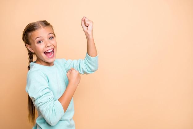 Ja! profielfoto van mooie opgewonden kleine dame ambitieus vuist heffen succes vieren verbaasd extatisch dragen blauwe trui geïsoleerd beige pastelkleur muur