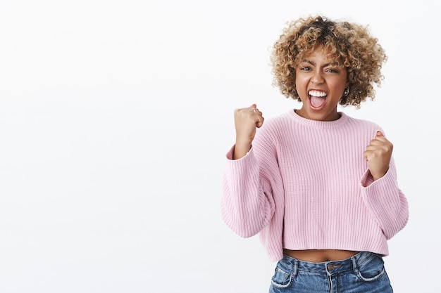 Ja schat, we hebben het gedaan. triomfantelijke en vrolijke knappe afro-amerikaanse vrouw schreeuwen van vreugde en geluk als winnende gebalde vuisten in overwinningsgebaar juichen over witte muur