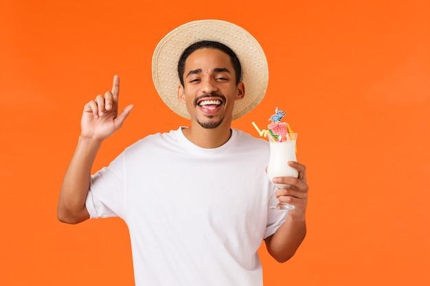 Ja vakantie rockt. vrolijke en zorgeloze, ontspannen afro-amerikaanse mannelijke toerist die plezier heeft met het drinken van alcohol, het houden van een cocktail en dansen in de discoclub van het hotel, oranje achtergrond