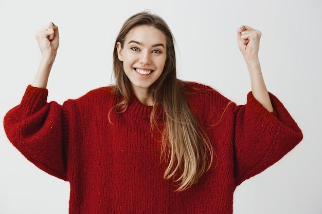 Ja, we hebben het gedaan, laten we beginnen met vieren. portret van positieve vrolijke knappe vrouwelijke student in losse trui, armen omhoog triomfantelijk, juichend vriend die eerste prijs won, breed glimlachend