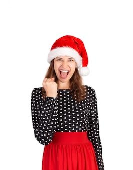 Ja we hebben het gedaan. portret van een vrouw in jurk vieren overwinning, verbaasd over winst. emotioneel meisje in de geïsoleerde kerstmishoed van de kerstman