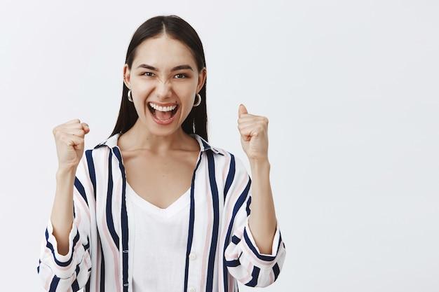 Ja, we hebben het gedaan. triomfantelijke gelukkige enthousiaste vrouw in gestreepte blouse, gebalde vuist opheffend en ja zeggen terwijl ze een succesvolle deal of overwinning viert, tevreden en opgewonden zijn over grijze muur