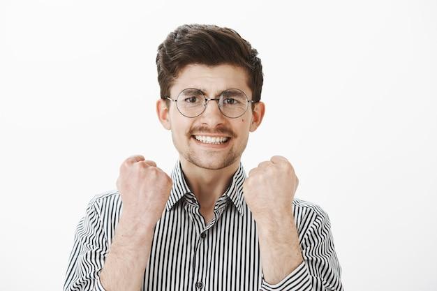 Ja, we hebben het project op tijd afgerond. portret van knap volwassen mannelijk model in brillen en gestreept overhemd, gebalde vuisten opheffen, zelfverzekerd zijn, succes en overwinning vieren over grijze muur
