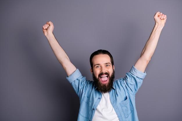 Ja, we winnen! actieve voetballiefhebber kerel kijken wedstrijd zijn favoriete team overwinning voelen opgetogen gekke emoties vuisten heffen schreeuwen ja draag stijlvolle kleding geïsoleerd over grijze kleur muur
