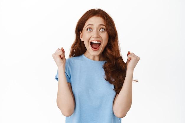Ja winnen. opgewonden roodharige meisje viert winnen, vuist pompgebaar maken en schreeuwen van vreugde en verbazing, triomferen, succes behalen, staande op wit