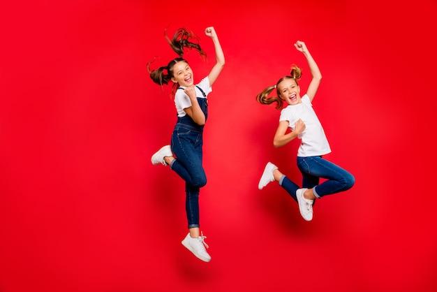 Ja, zwarte vrijdag kortingen! volledige grootte foto van opgetogen twee gekke vriendinnen winnen loterij, heffen vuisten, schreeuwen, springen dragen wit t-shirt denim jeans overall geïsoleerde rode kleur achtergrond
