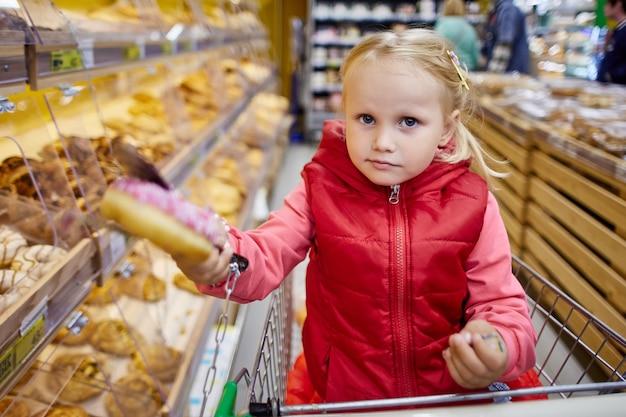 Jaar oud meisje in winkelwagen houdt donute op marktplaats