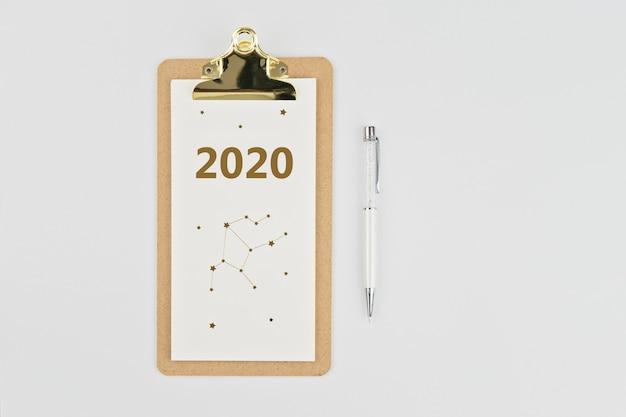 Jaarlijkse kalender 2020 klembord notebook en pen op wit