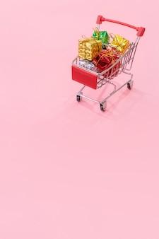 Jaarlijkse verkoop, kerstinkopen seizoen concept. mini rode winkelwagen trolley vol geschenkdoos geïsoleerd op bleke roze achtergrond