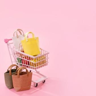 Jaarlijkse verkoop shopping seizoen concept - mini rode winkelwagen trolley vol papieren zak cadeau geïsoleerd