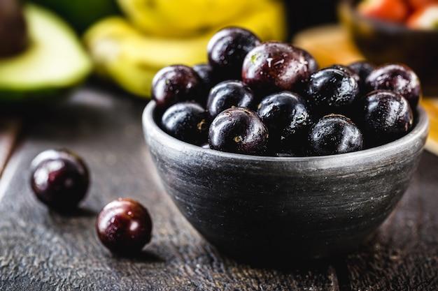 Jabuticaba, een zeldzame druif uit zuid-amerika, op een rustieke tafel met fruit op de achtergrond