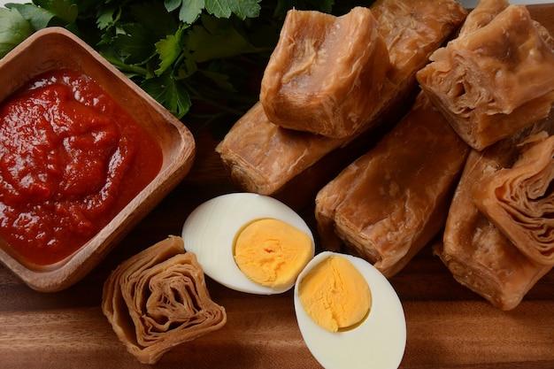 Jachnun of jahnun, jemenitisch joods gebak, geserveerd met vers geraspte tomaat en gekookt ei en zhug, afkomstig van de adeni-joden, en traditioneel geserveerd op shabbat-ochtend in israël.