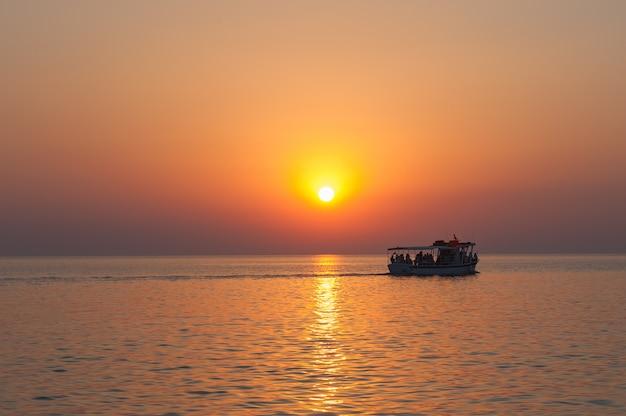 Jacht, boot, boot aan de horizon en het silhouet van een prachtige zonsondergang, hete zonsondergang. cruise schip