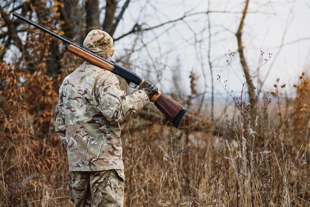Jacht, oorlog, leger en mensen concept - jonge soldaat, boswachter of jager met geweer wandelen in het bos