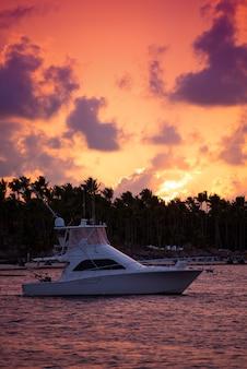 Jacht op zee tegen de lucht, palmbomen, wolken en zon bij zonsondergang.