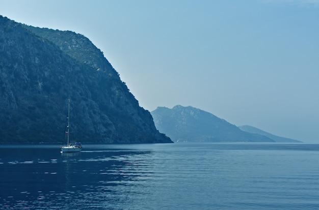 Jacht vaart op zee langs de bergen