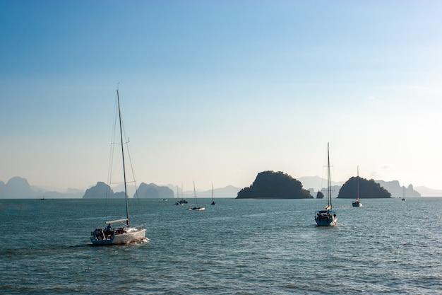 Jachten en catamarans met zeilen gaan de zee op tegen de achtergrond van rotsachtige eilanden aan de horizon