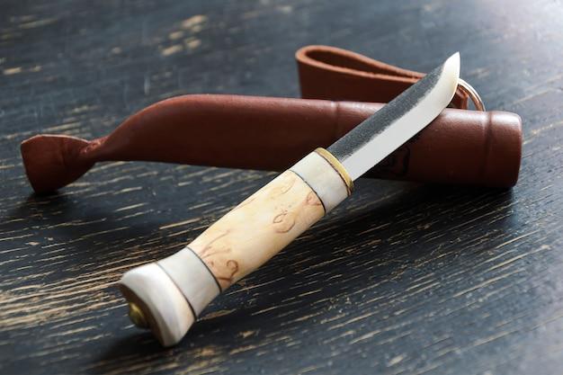 Jachtmes met kort lemmet en benen handvat met leren etui op donkere shabby houten tafel.