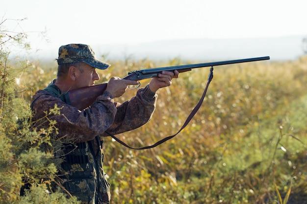 Jachtperiode, herfstseizoen geopend. een jager met een pistool in zijn handen in jachtkleding in het herfstbos op zoek naar een trofee. een man staat met wapens en jachthonden het wild op te sporen.