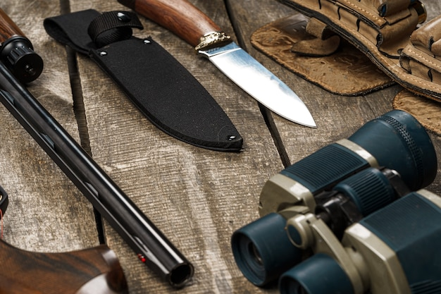 Jachtuitrusting op oude houten achtergrond inclusief geweermes verrekijkers en cartridges