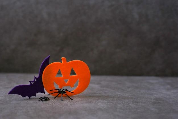 Jack o lantern en bat gemaakt van vilt naast spinnen op bruine achtergrond