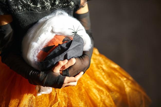 Jack o lantern, halloween pompoen in medische bescherming zwart masker in meisjeshanden tijdens halloween-feest thuis covid19 coronavirus pandemie, kopie ruimte